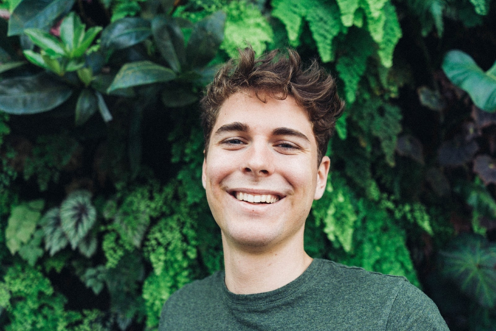 man smiling while standing near plants