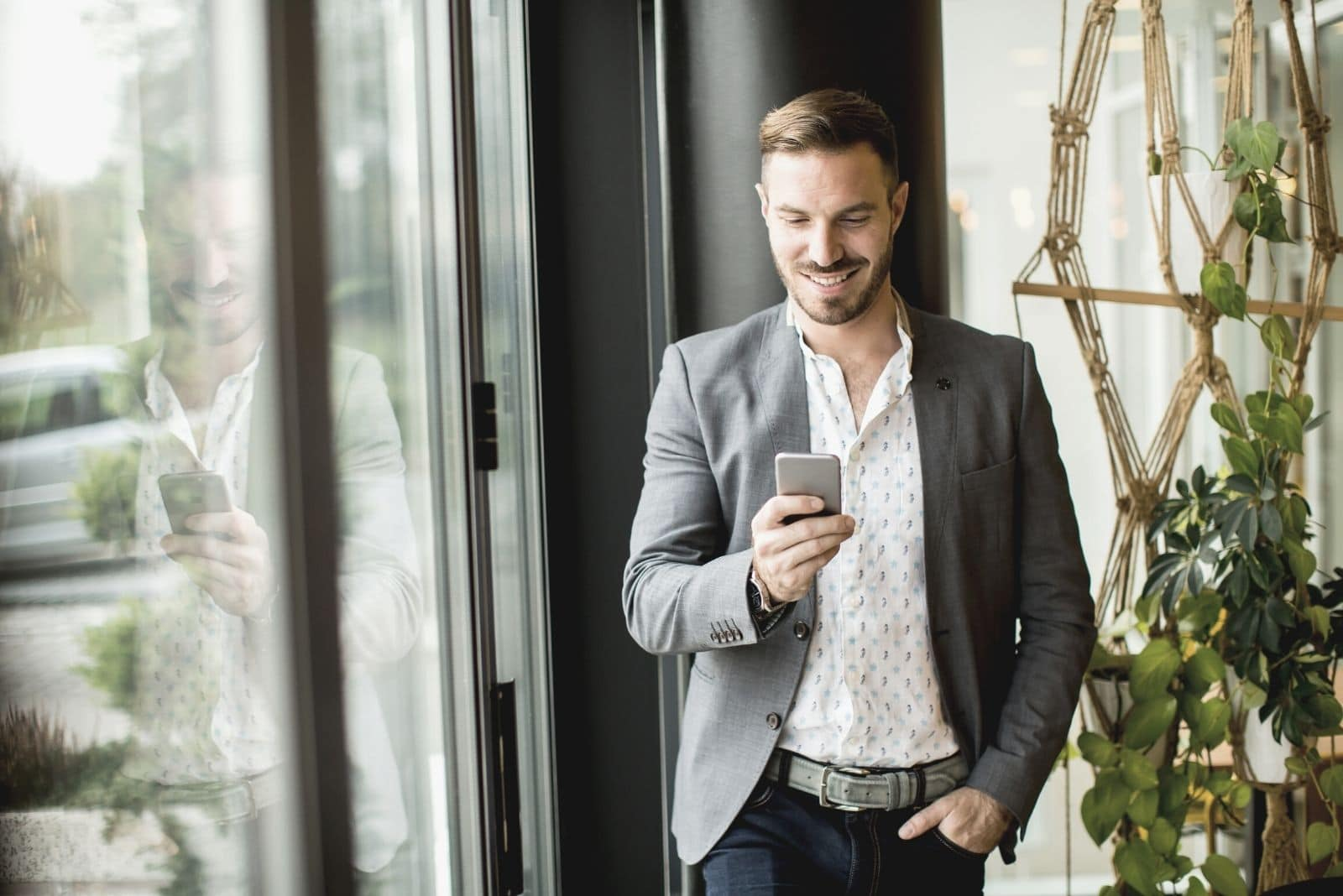 man standing inside the office smiling and looking at his phone with one hand on his pocket