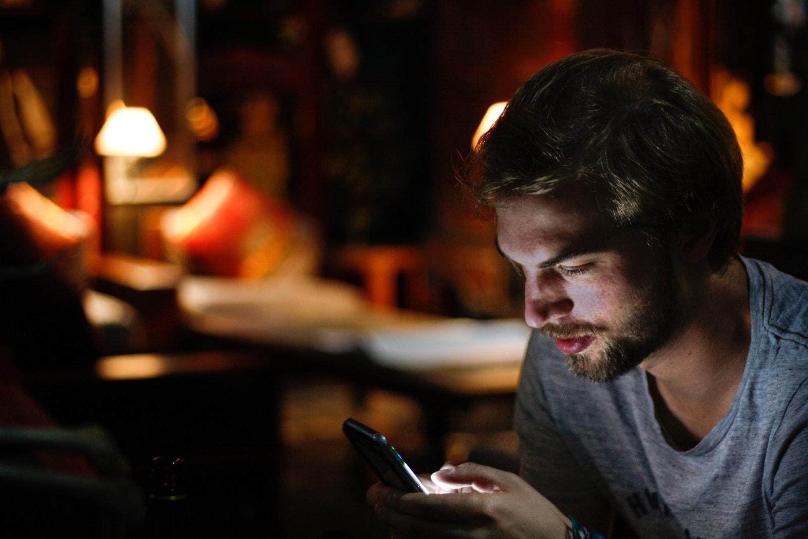 man in gray t-shirt using phone indoor