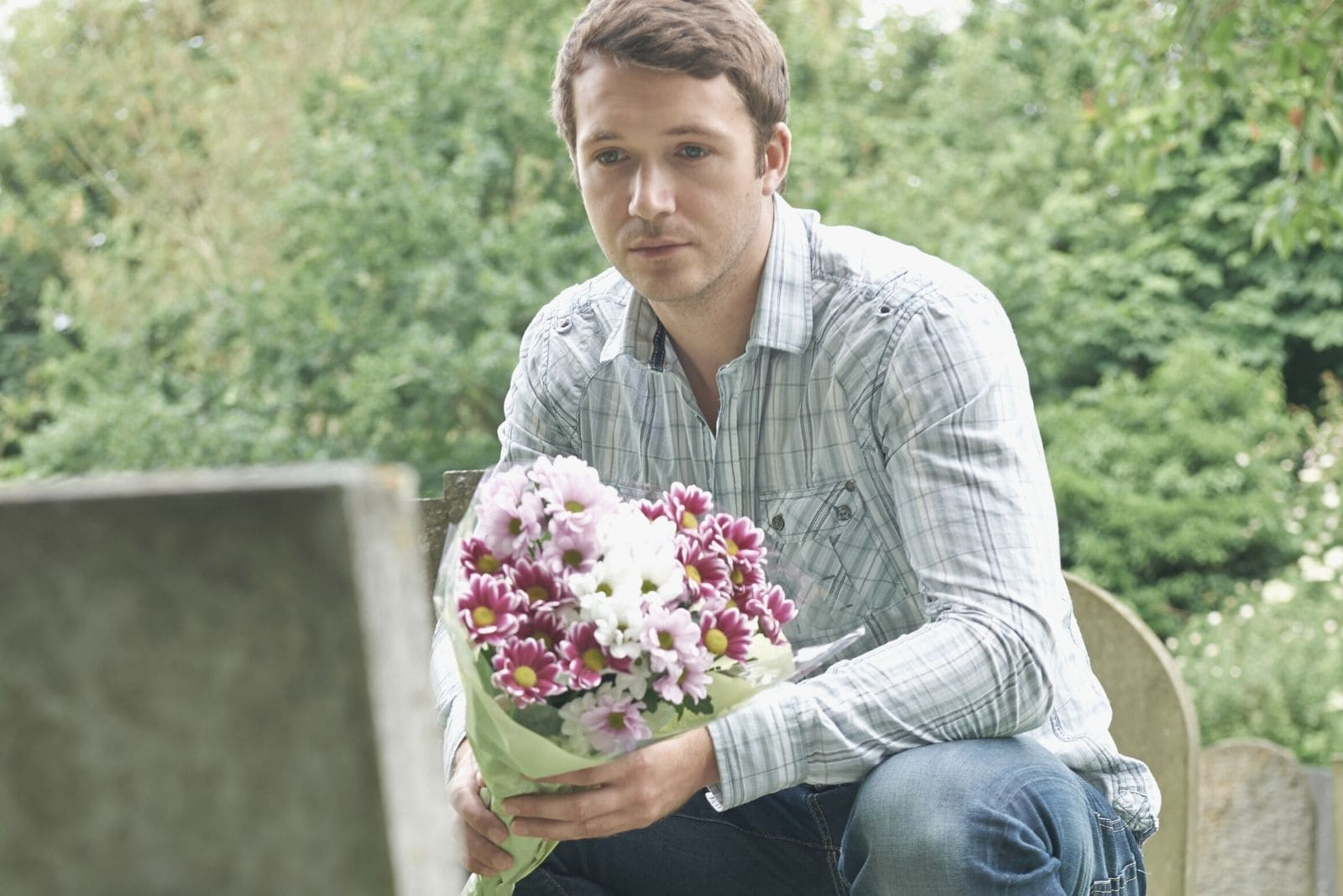 man visiting grave of his loved one brininging a buoquet of flowers