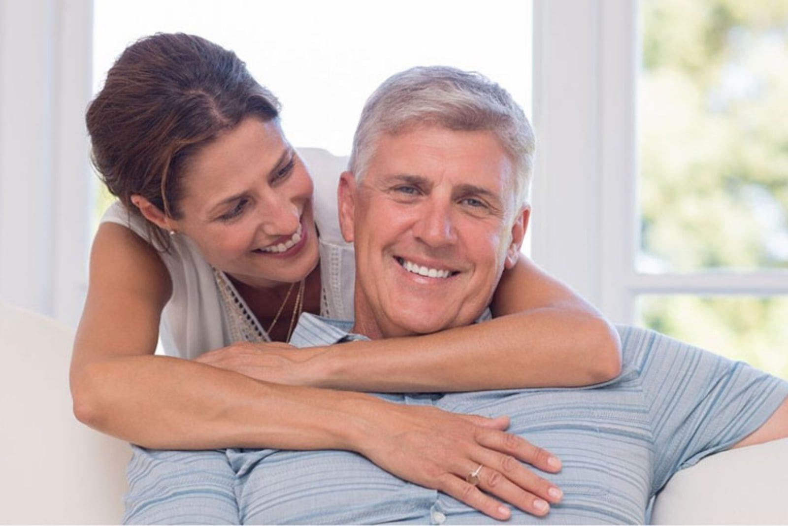 mature man sitting hugged by a younger woman inside the living room