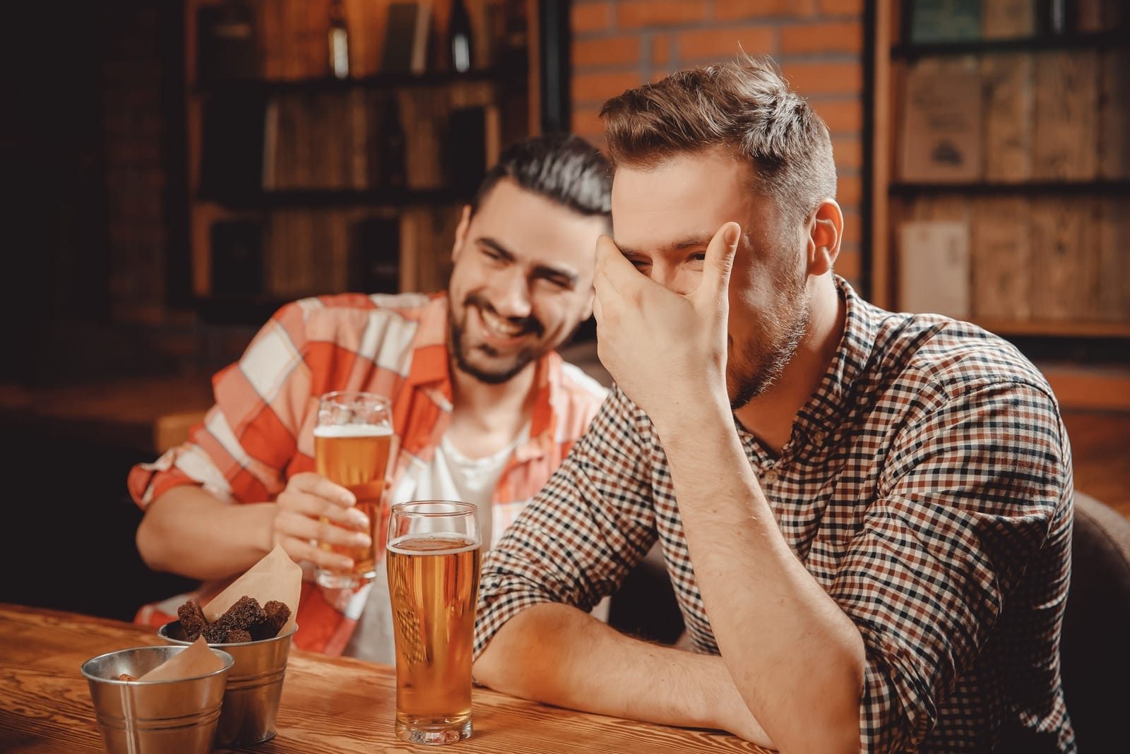 two men laughing while drinking beer