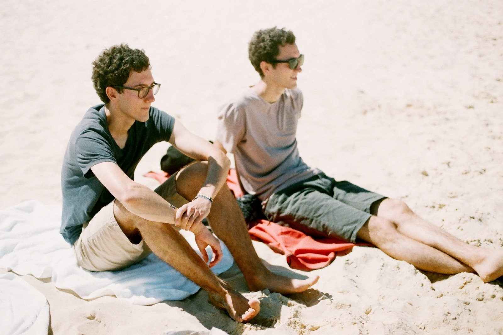 two men sitting on beach during daytime