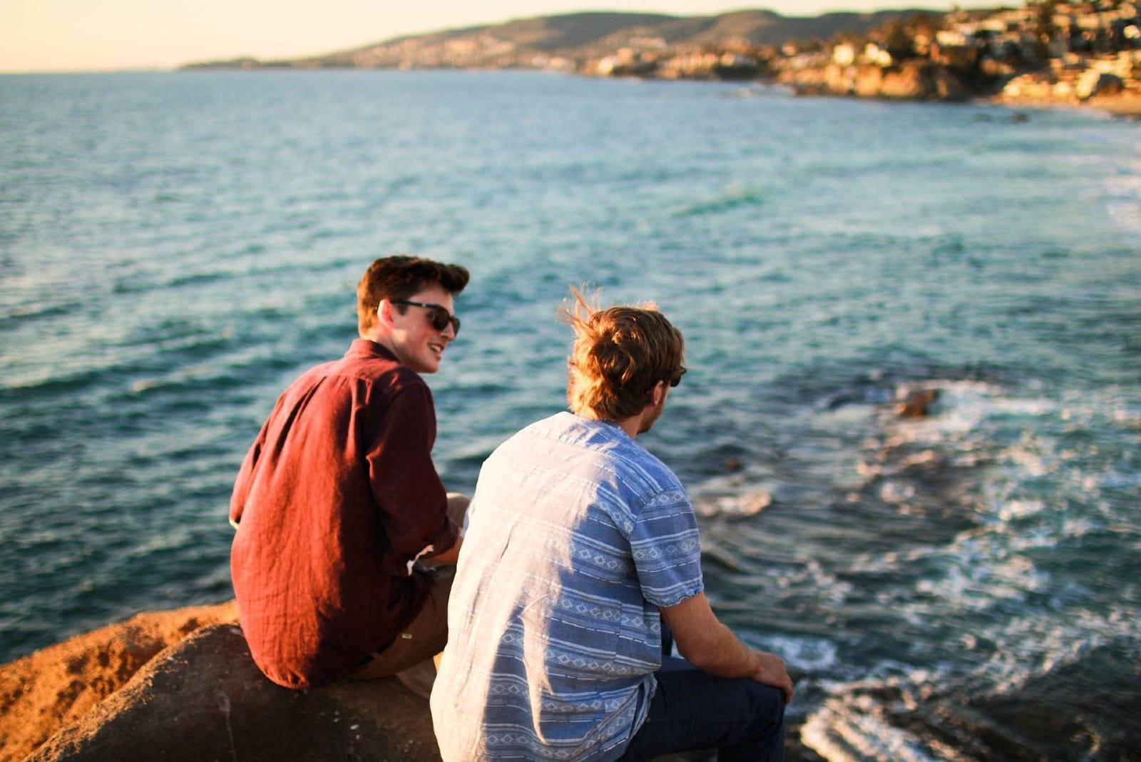 two men sitting on rock near sea