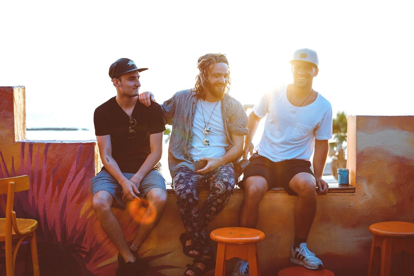 three men talking while sitting outdoor