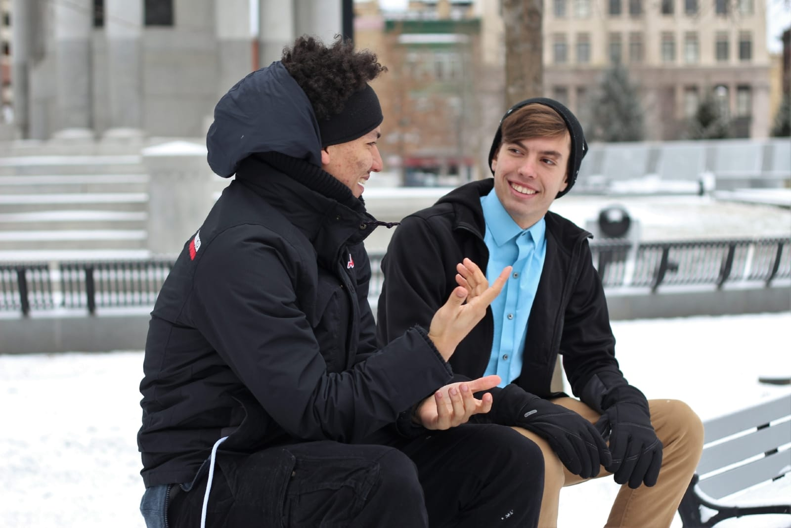 two men talking while sitting outdoor in winter