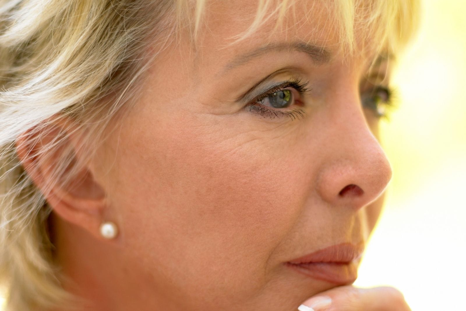 mid adult woman thinking with blonde hair focussed on the head