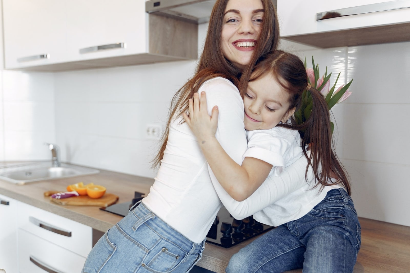 mother and daughter hugging in the kitchen