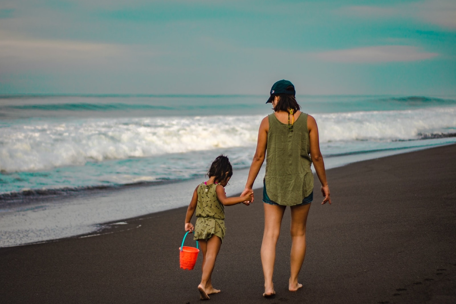mother and daughter holding hands while walking on shore