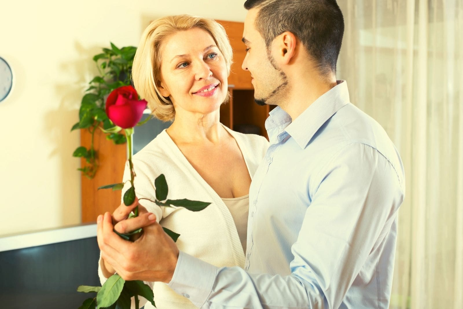 older woman dancing with a young man holding a rose inside the living room
