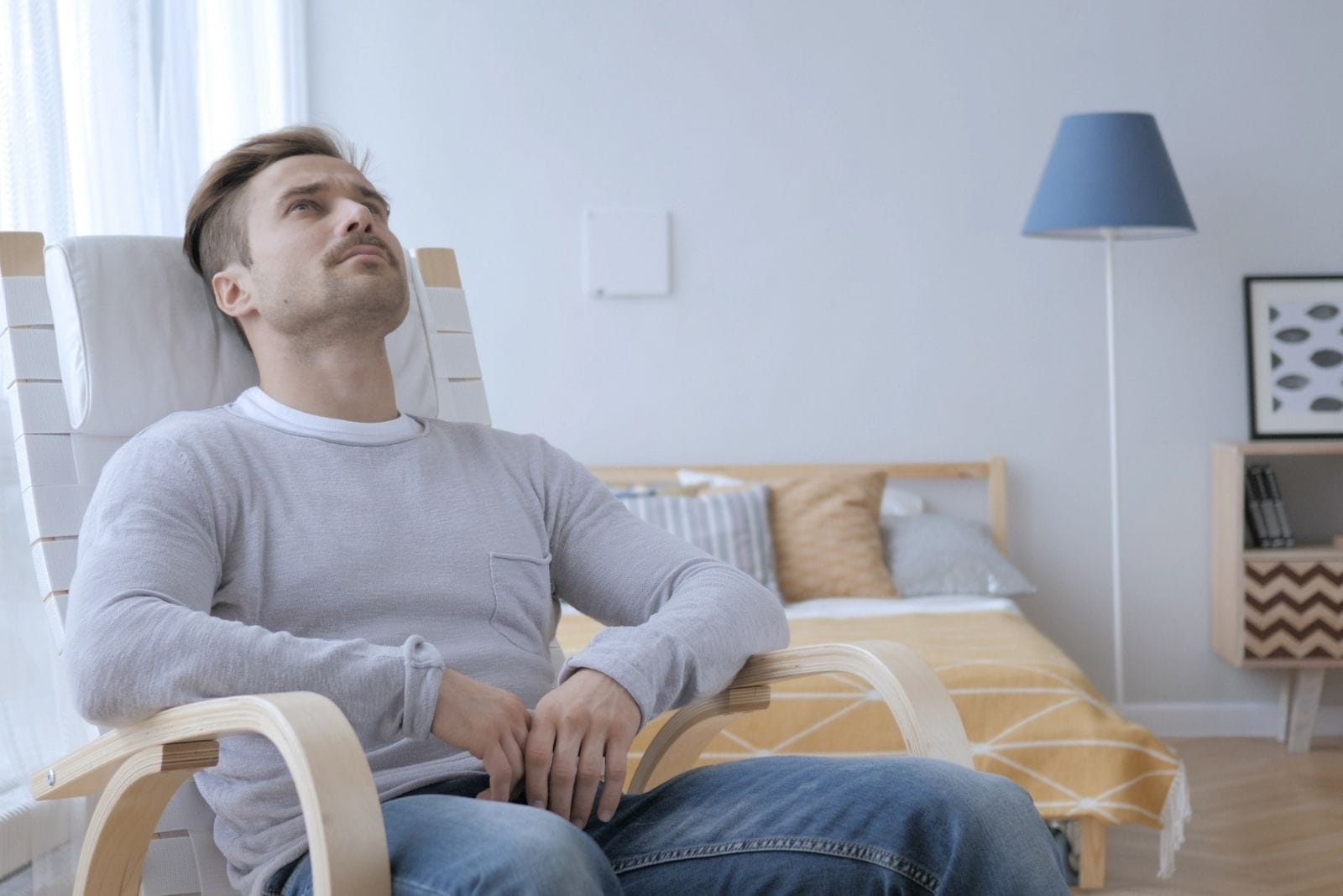 pensive adult man sitting on the chair inside the bedroom looking at the roof