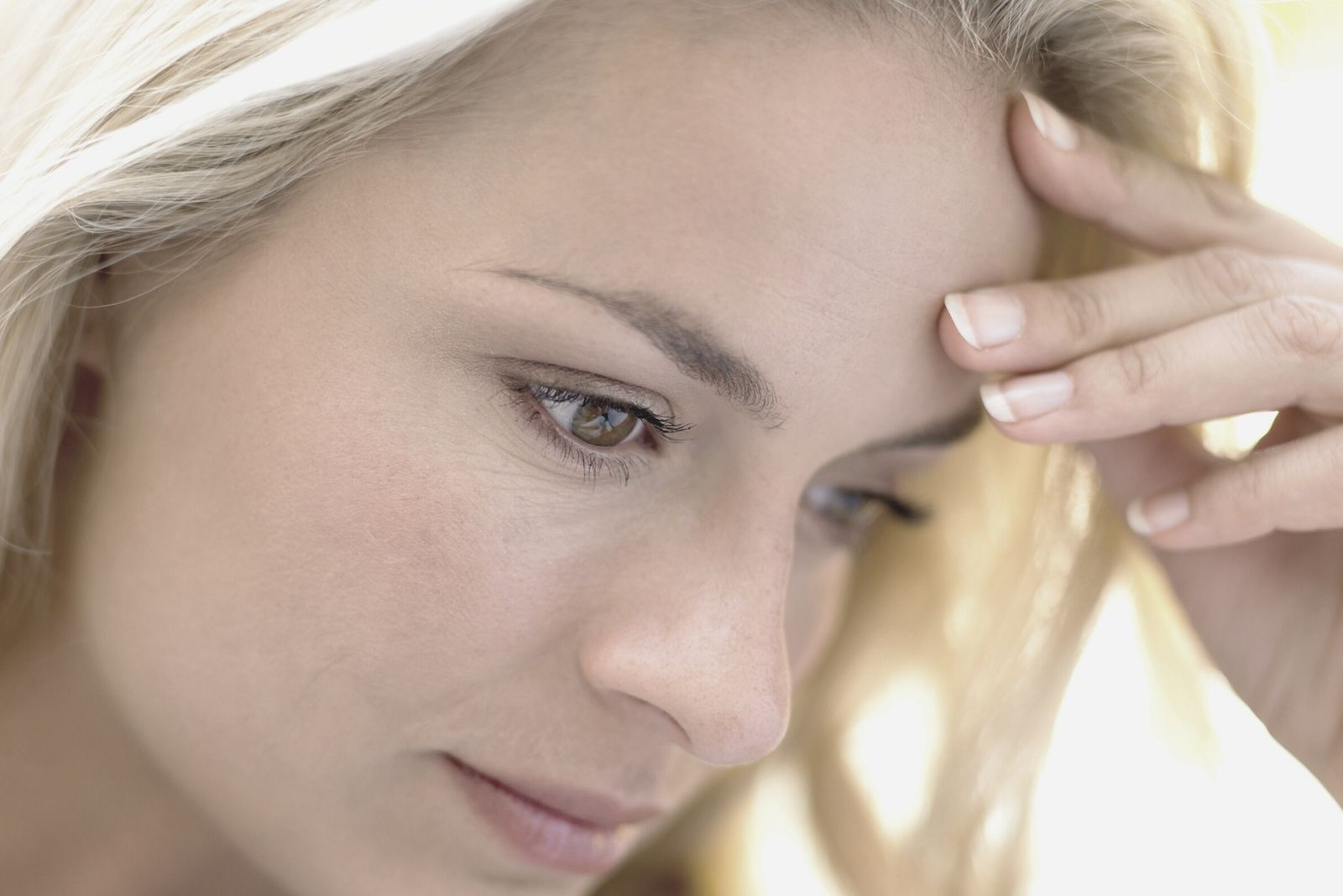 pensive blonde woman looking down and holding her head focus on her face