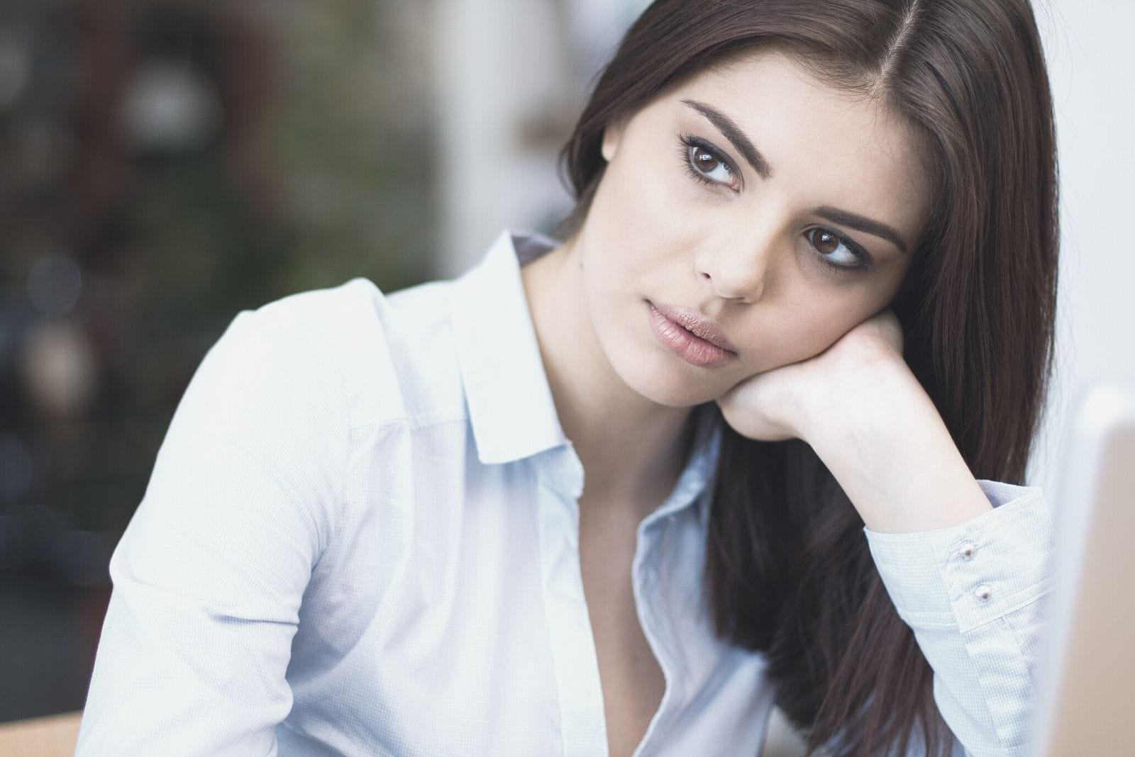 pensive businesswoman looking away and leaning her head to her hand