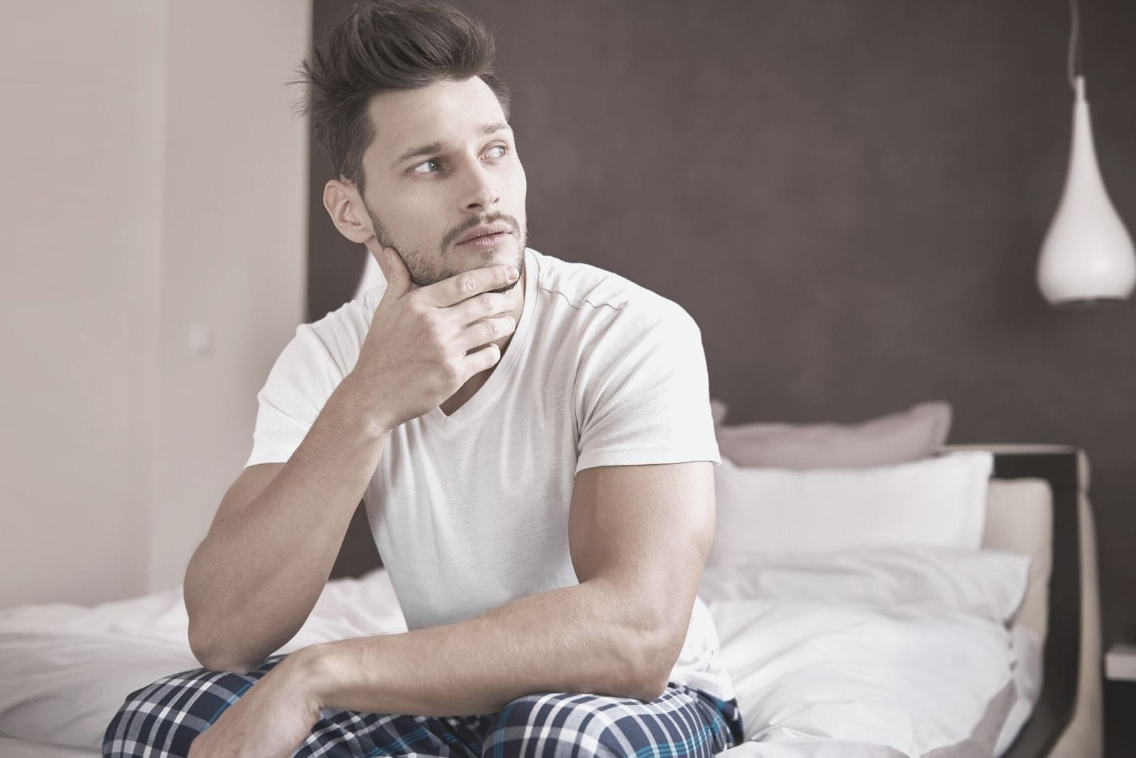 pensive man sitting at the edge of the bed inside the bedroom on his pajamas