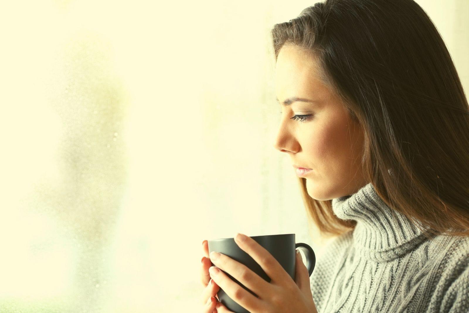 pensive sad woman drinking coffee near the glass window looking away