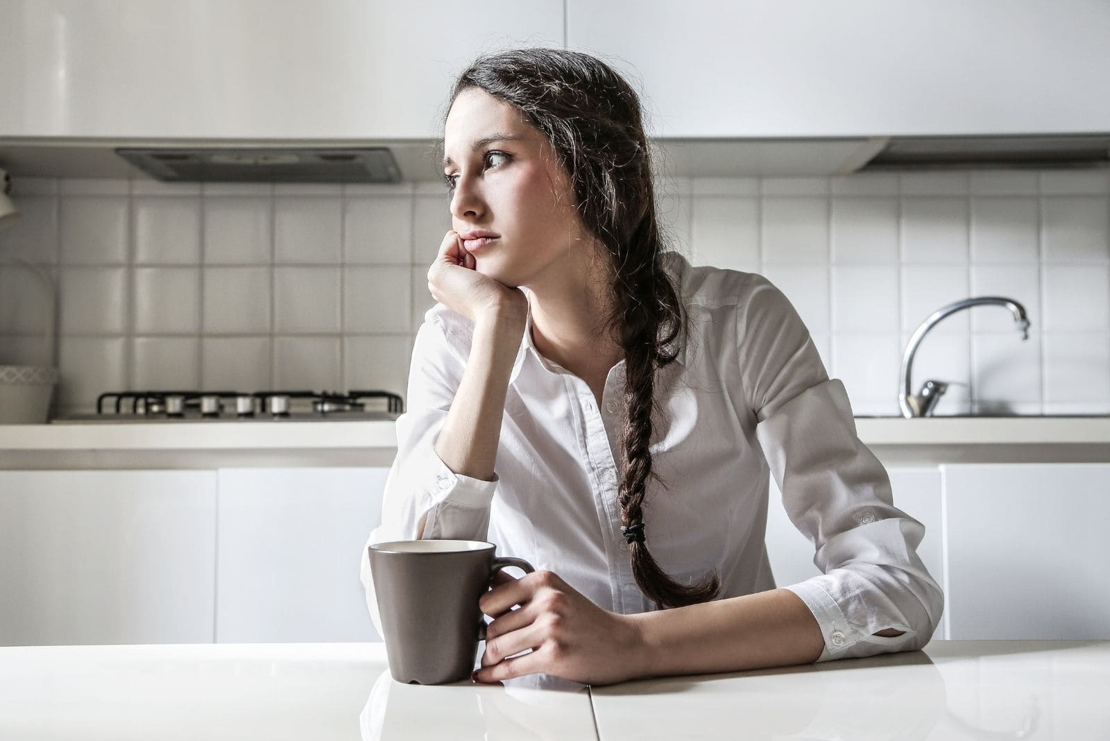 pensive woman drinking coffee in the kitchen looking away