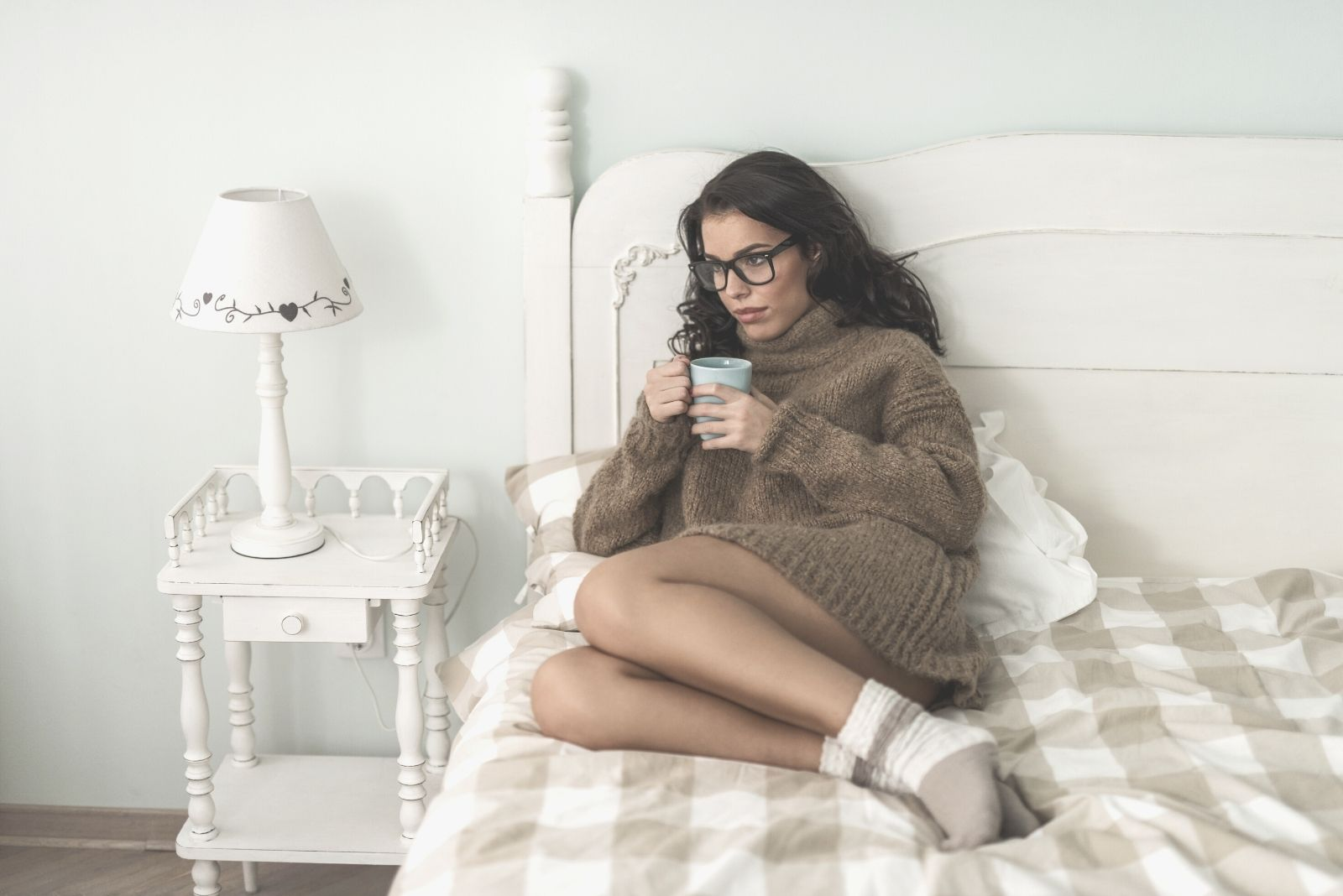 pensive woman in bed drinking coffee wearing eyeglasses and socks in the morning