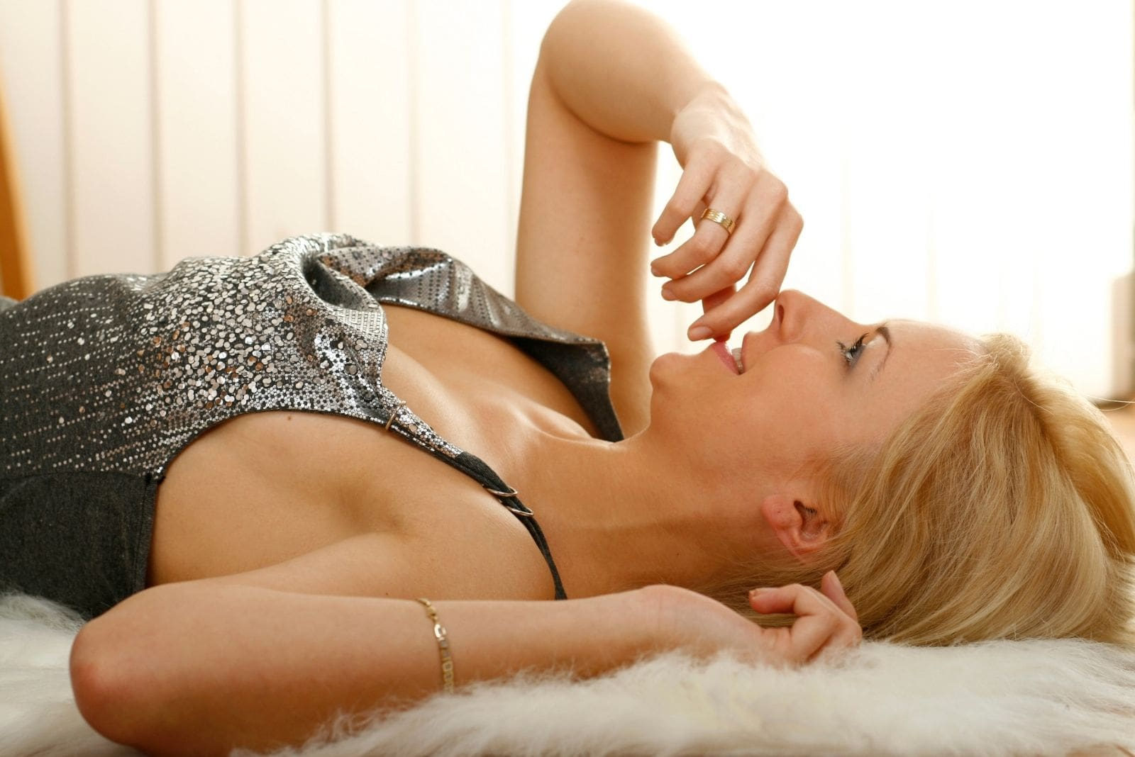 pensive woman lying down in bed wearing great dress and biting her nail