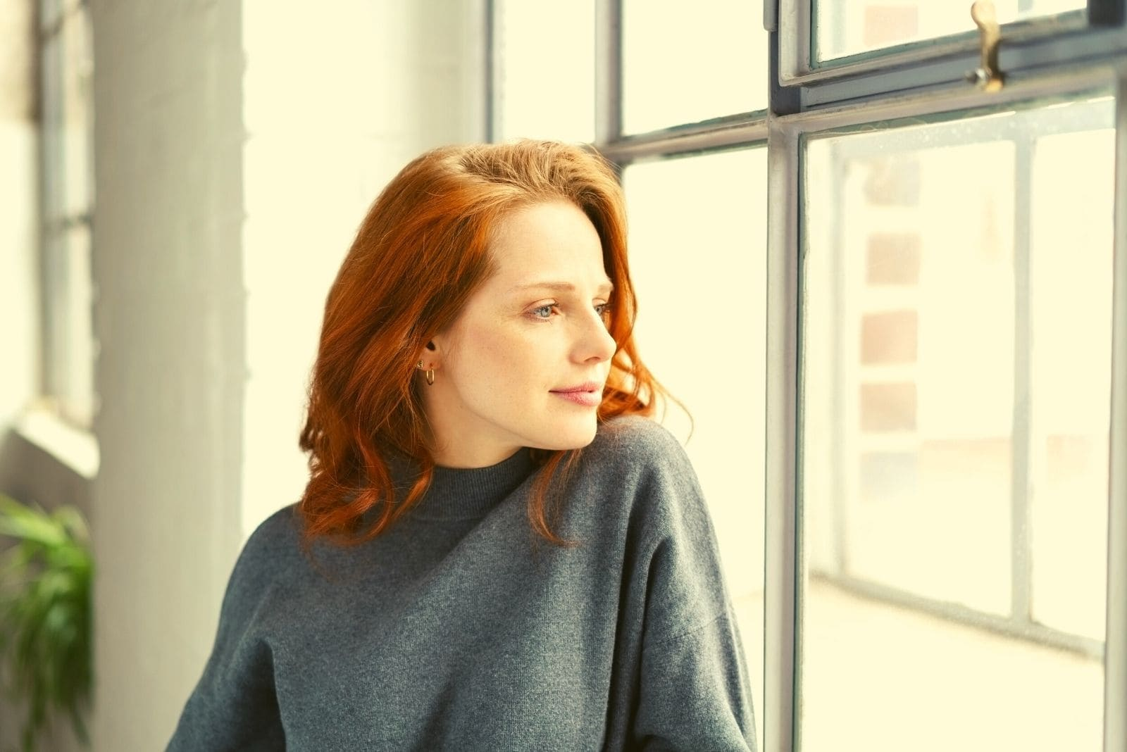 pensive woman smiling and standing near the window looking away