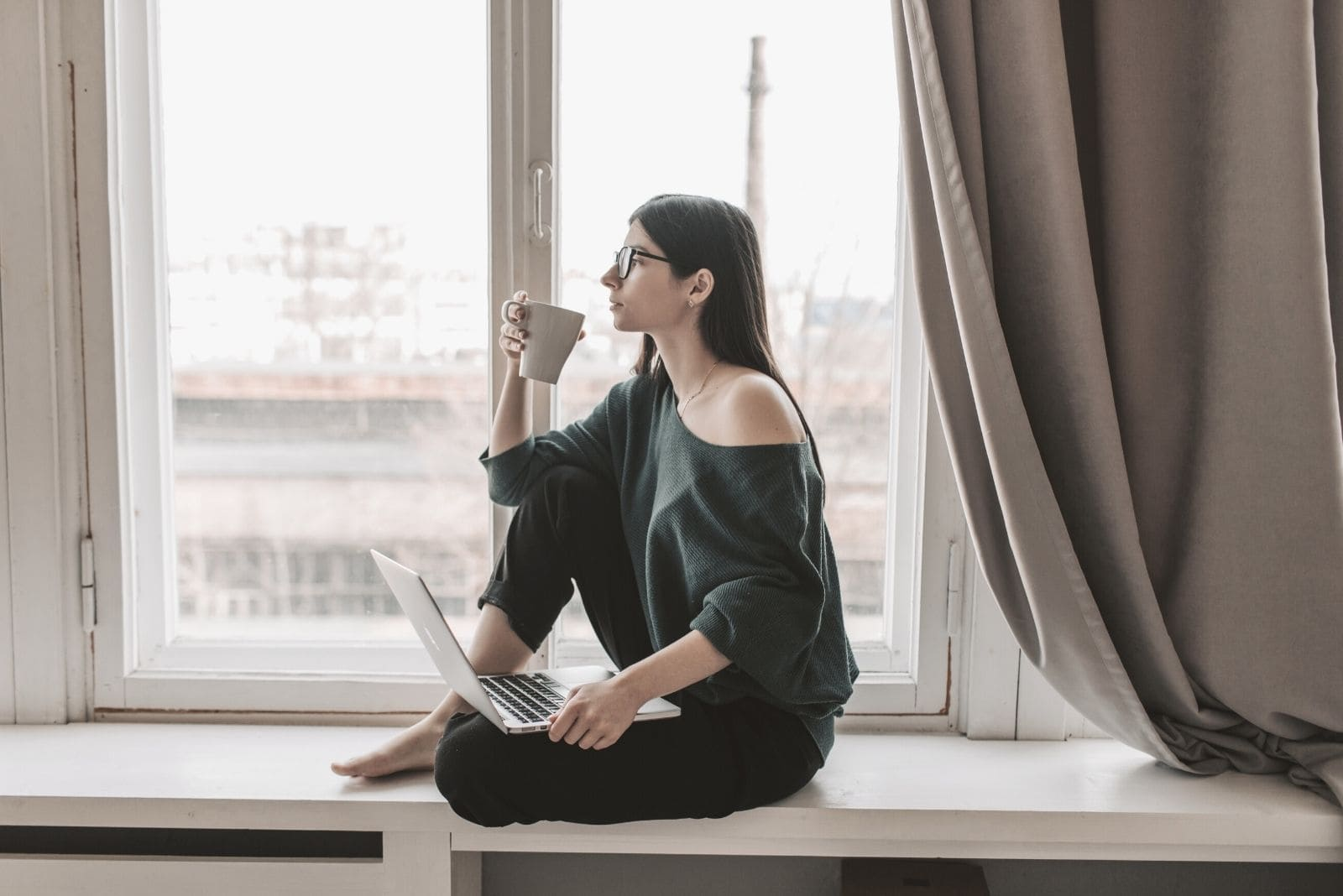 pensive woman with laptop drinking hot beverage sitting on the window sill