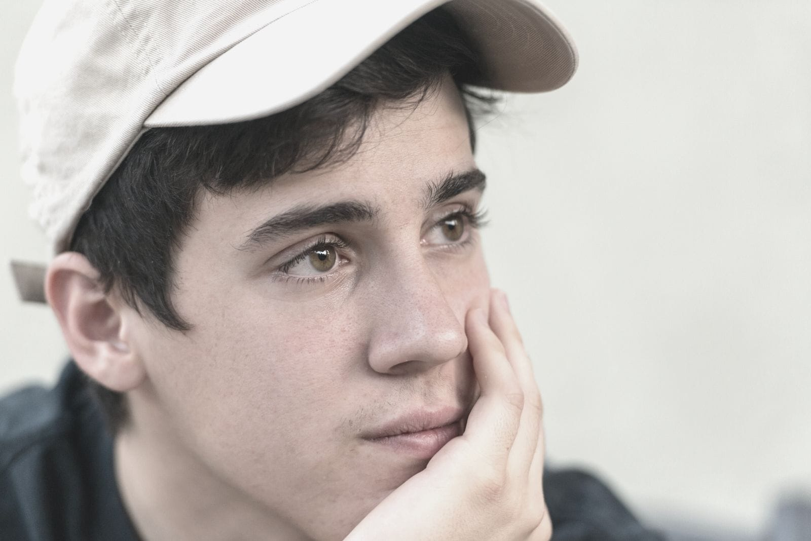pensive young man looking away wearing a cap