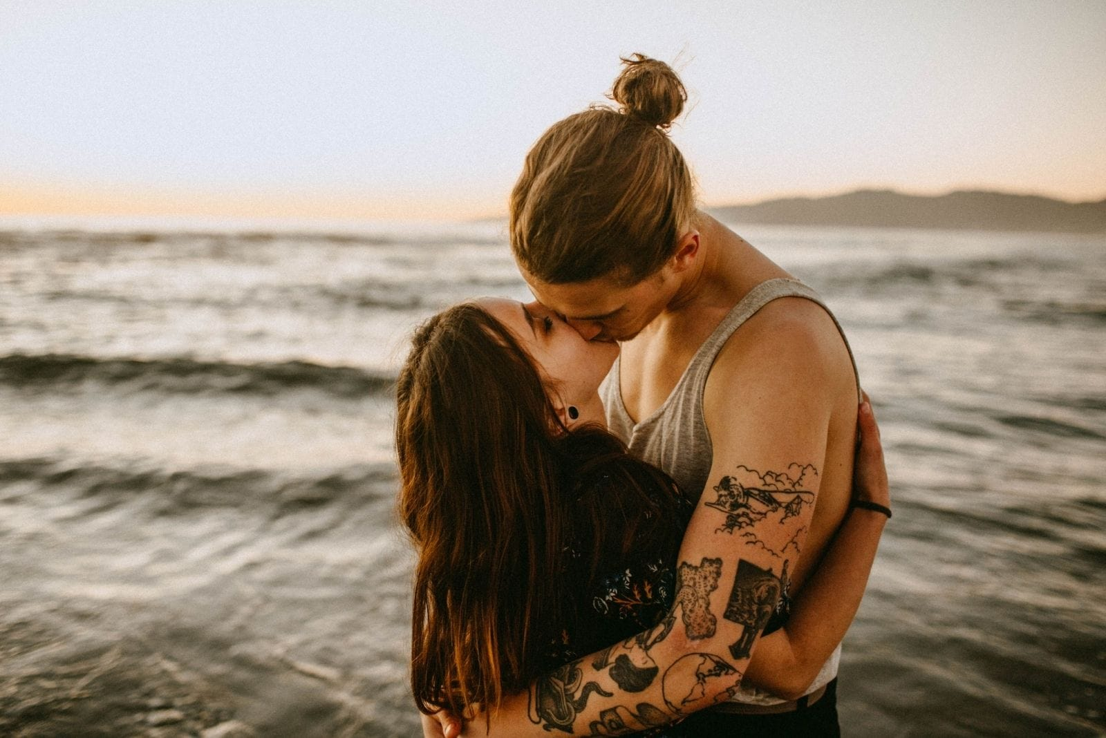 photo of kissing couple in the middle of the waters outdoors during the day