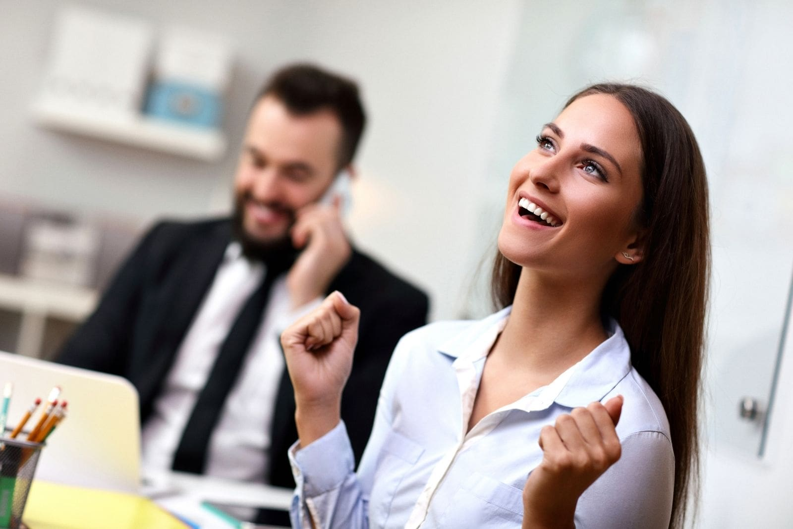 picture of a successful woman in the office and a man calling on the phone at the back