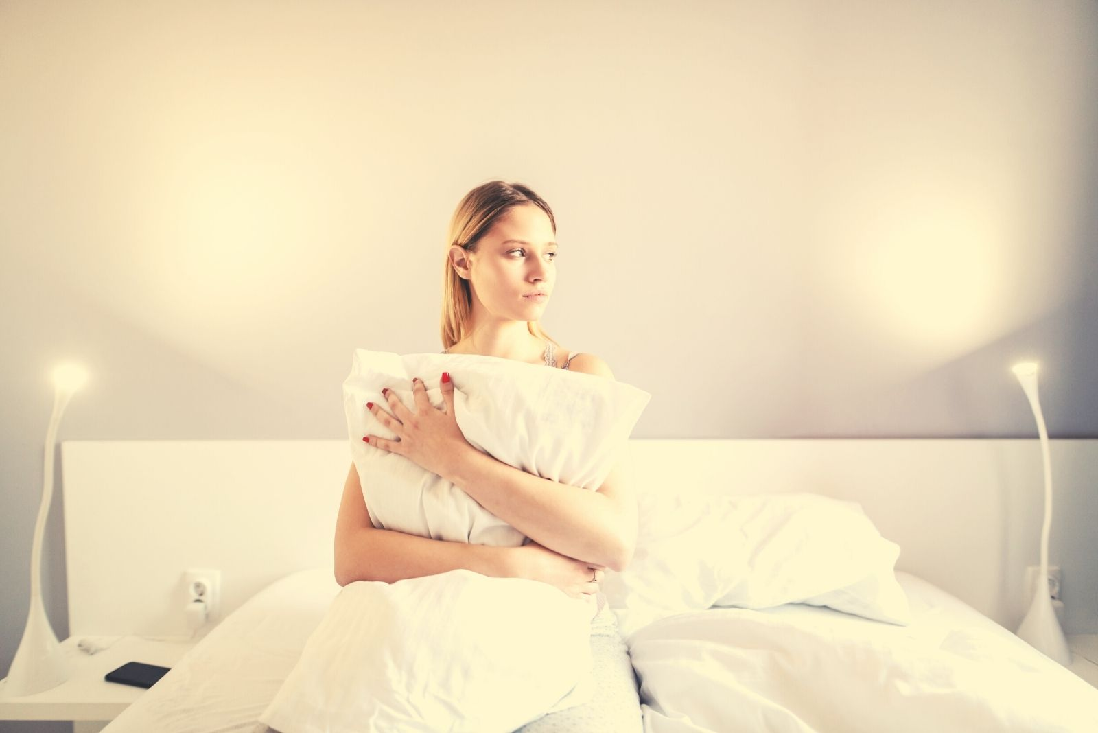 portrait of a sad woman embracing pillow while sitting in the bed