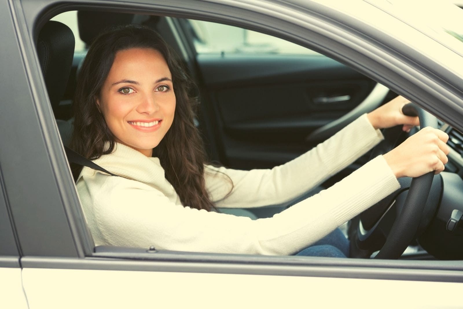 pretty woman driving and smiling to the camera wearing long sleeved shirt