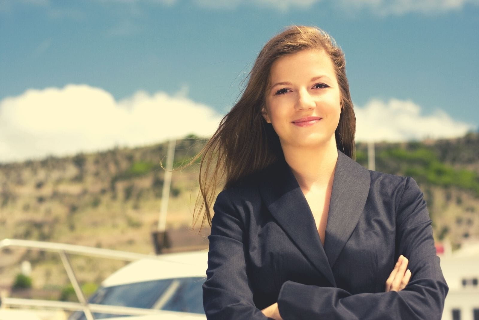 pretty woman standing near a boat with arms crossed and smiling