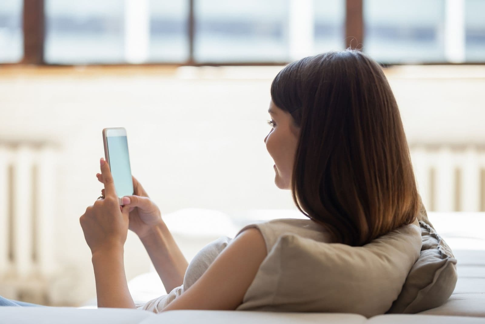 rear view of a woman browsing thru her smartphone chilling in the couch of the living room