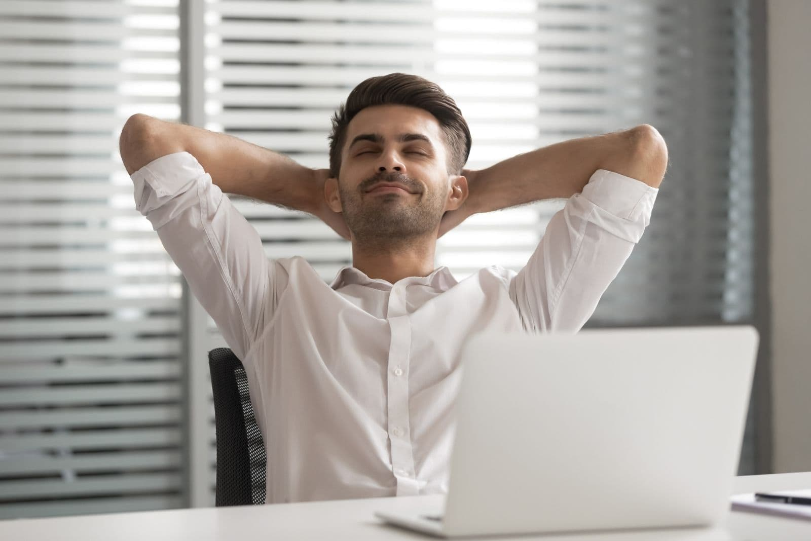 relaxed positive calm man sitting by the office table with both hands at the back of his head