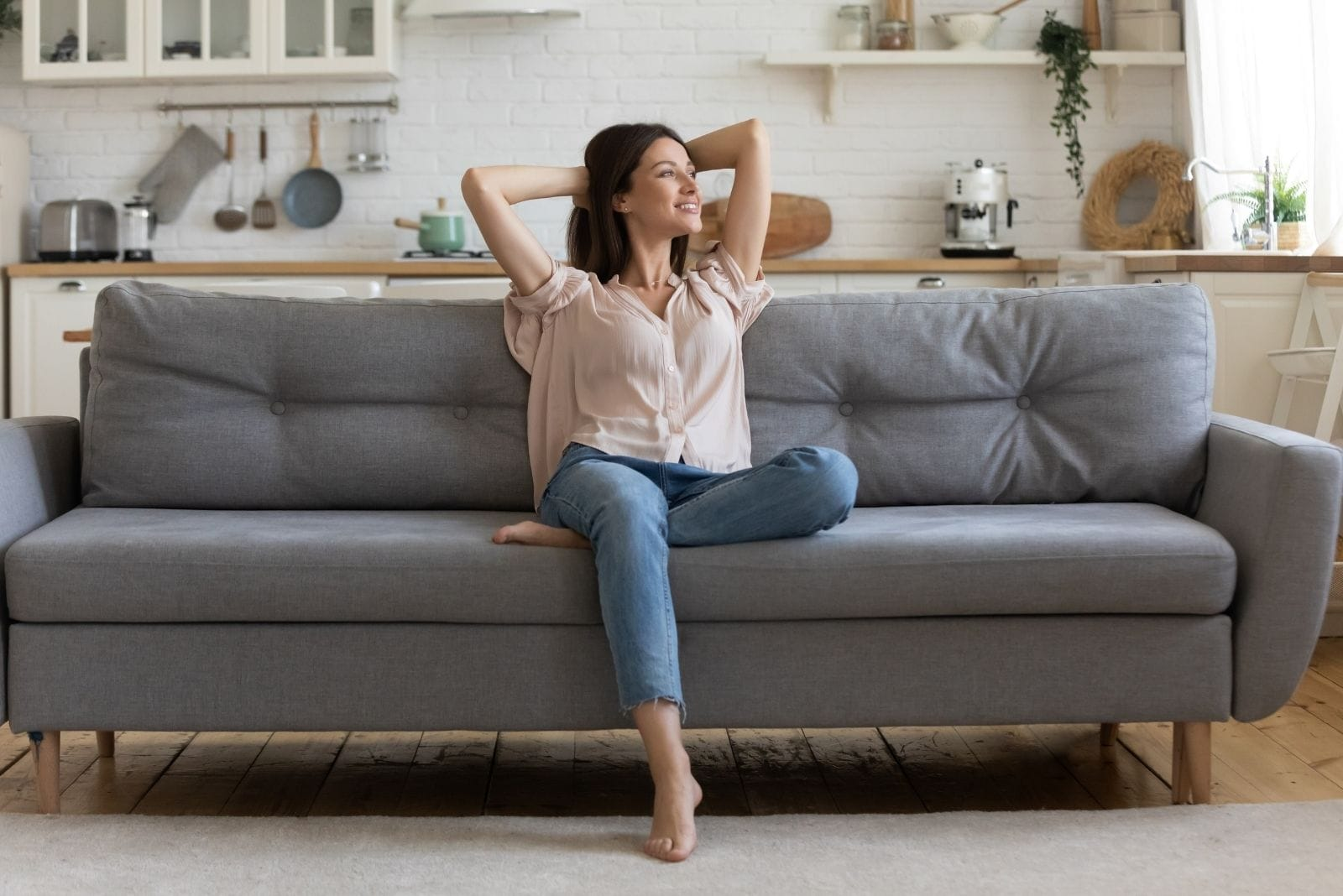 relaxed woman sitting on the gray sofa looking away inside the living room