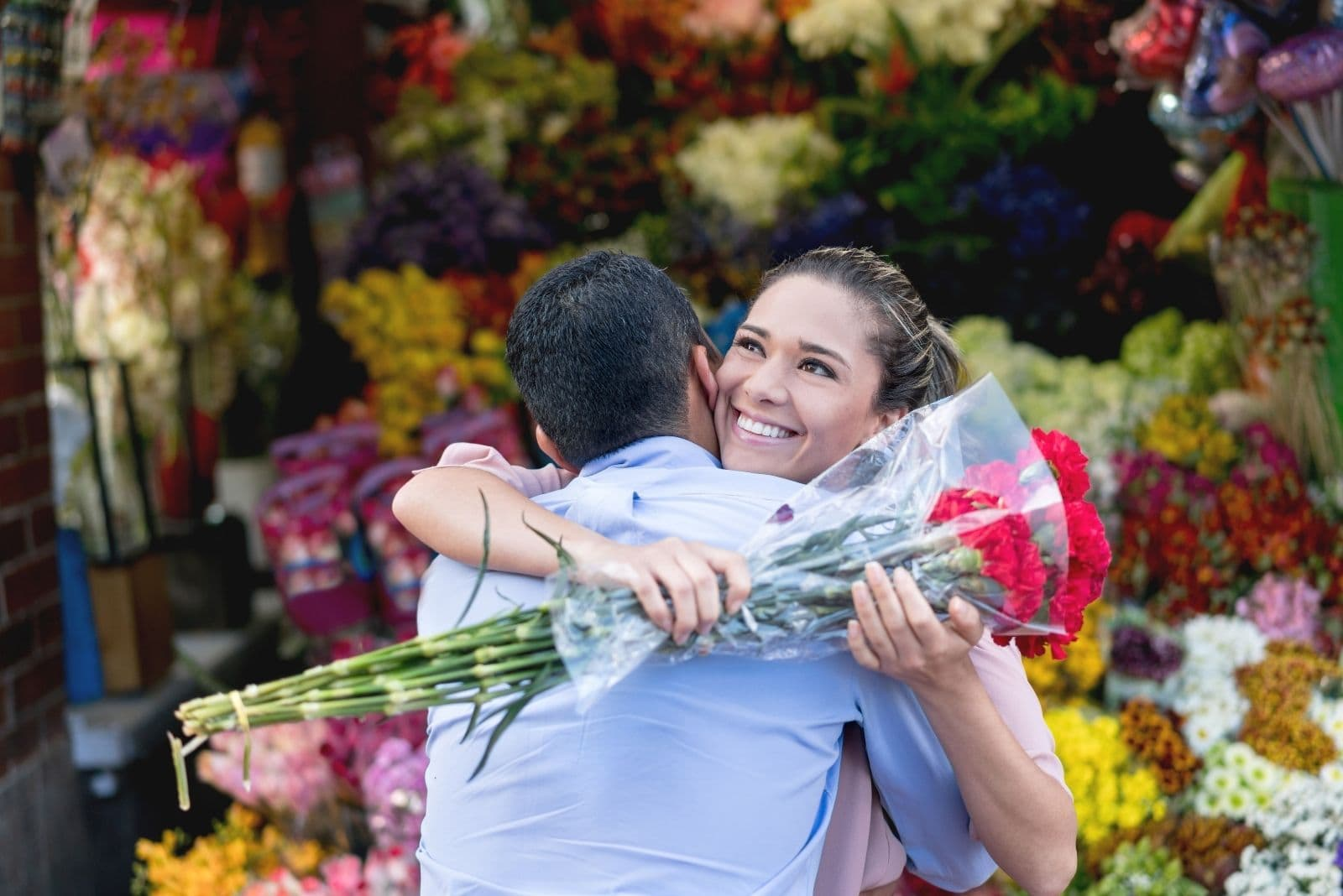 romantic couple giving flower hugging the man near the flower shop