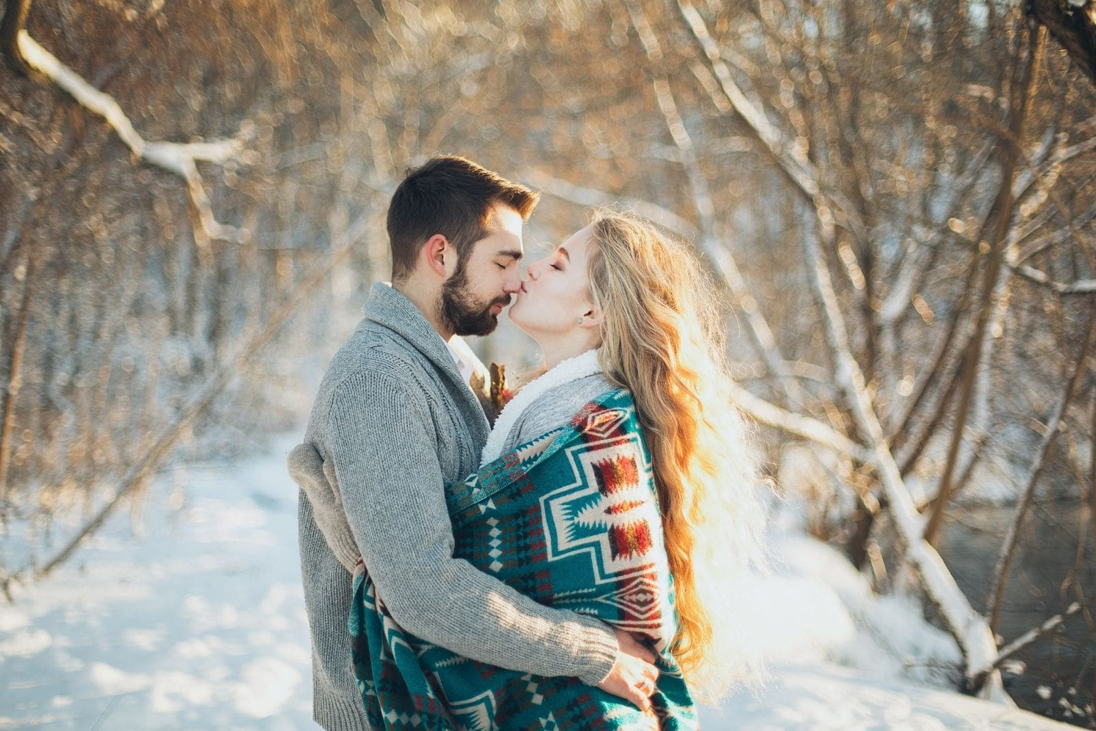 romantic man and woman kissing covered with thick clothed around hugging in the middle of winter forest