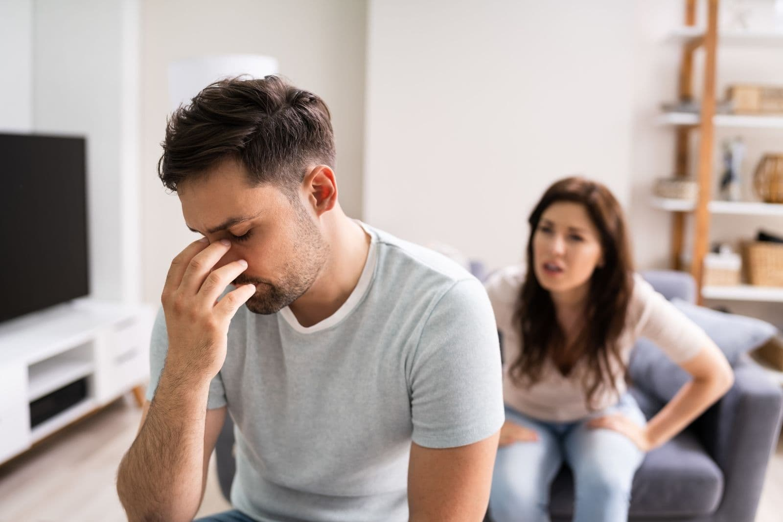 sad man having headache while wife nags him inside living room