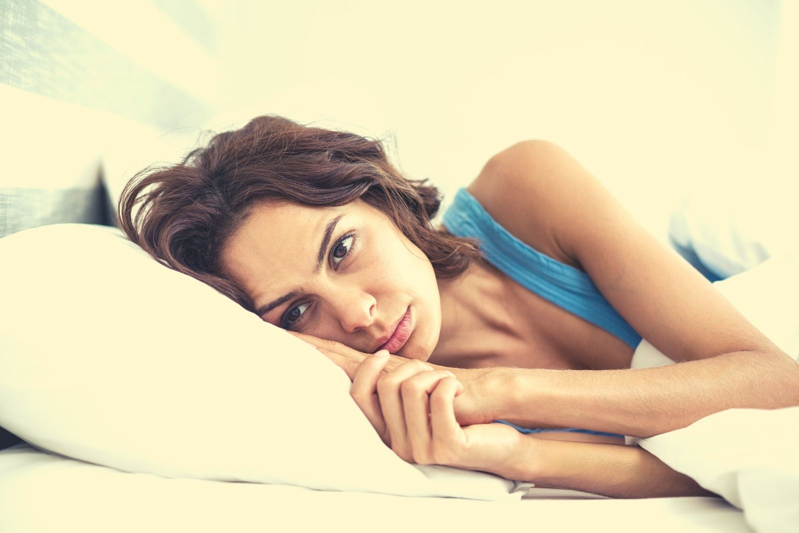 sad woman lying on her right side in bed wearing blue tank top