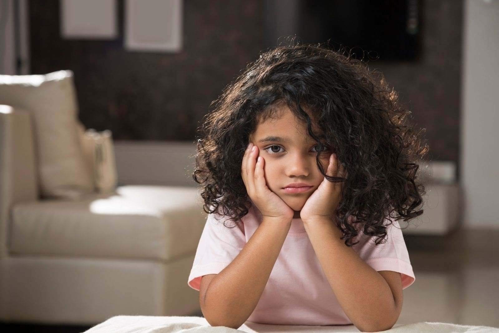 sadness in the eyes of the child looking at the camera sitting inside livingroom