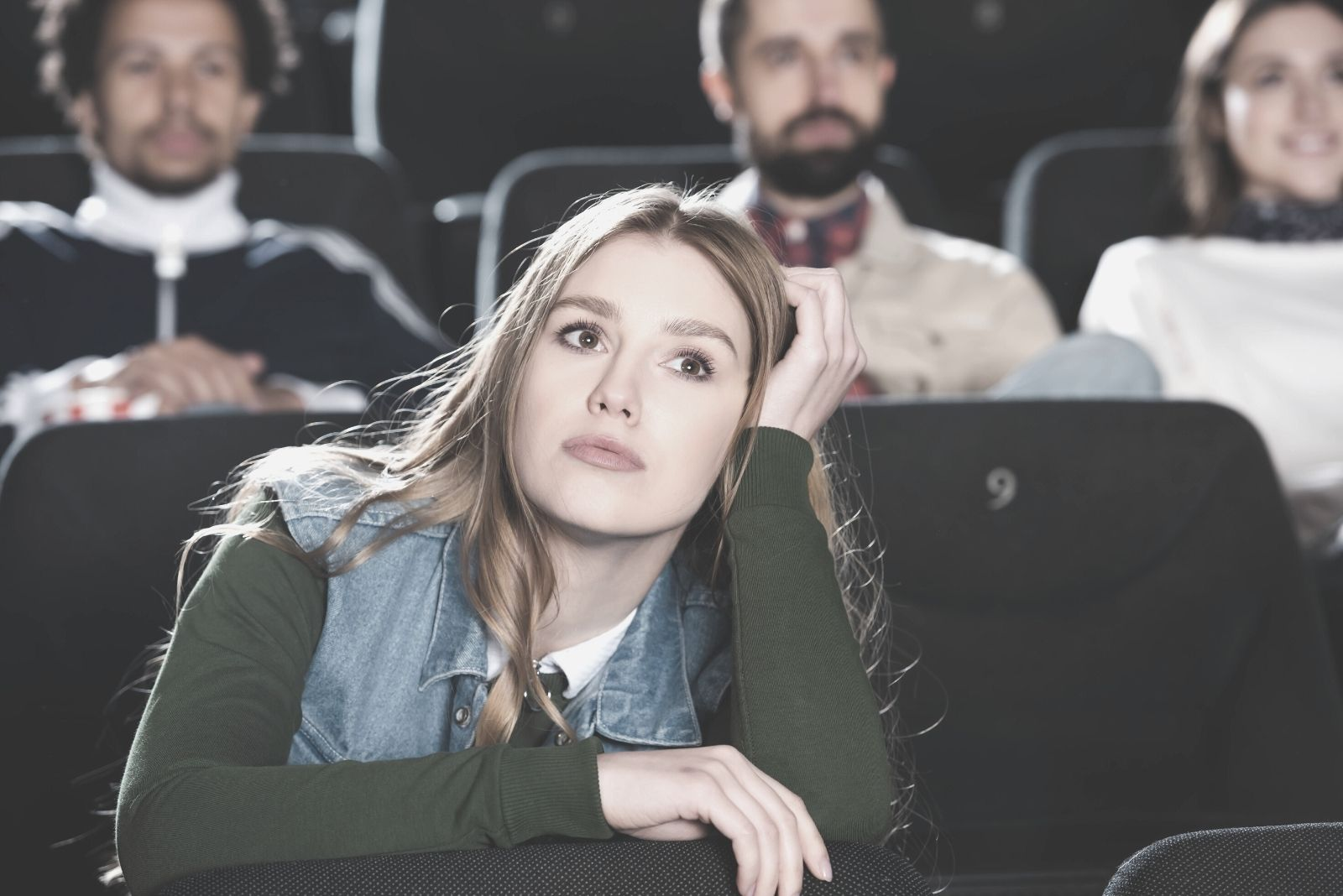 selective focus of a woman watching movie alone with few people at the back inside the cinema