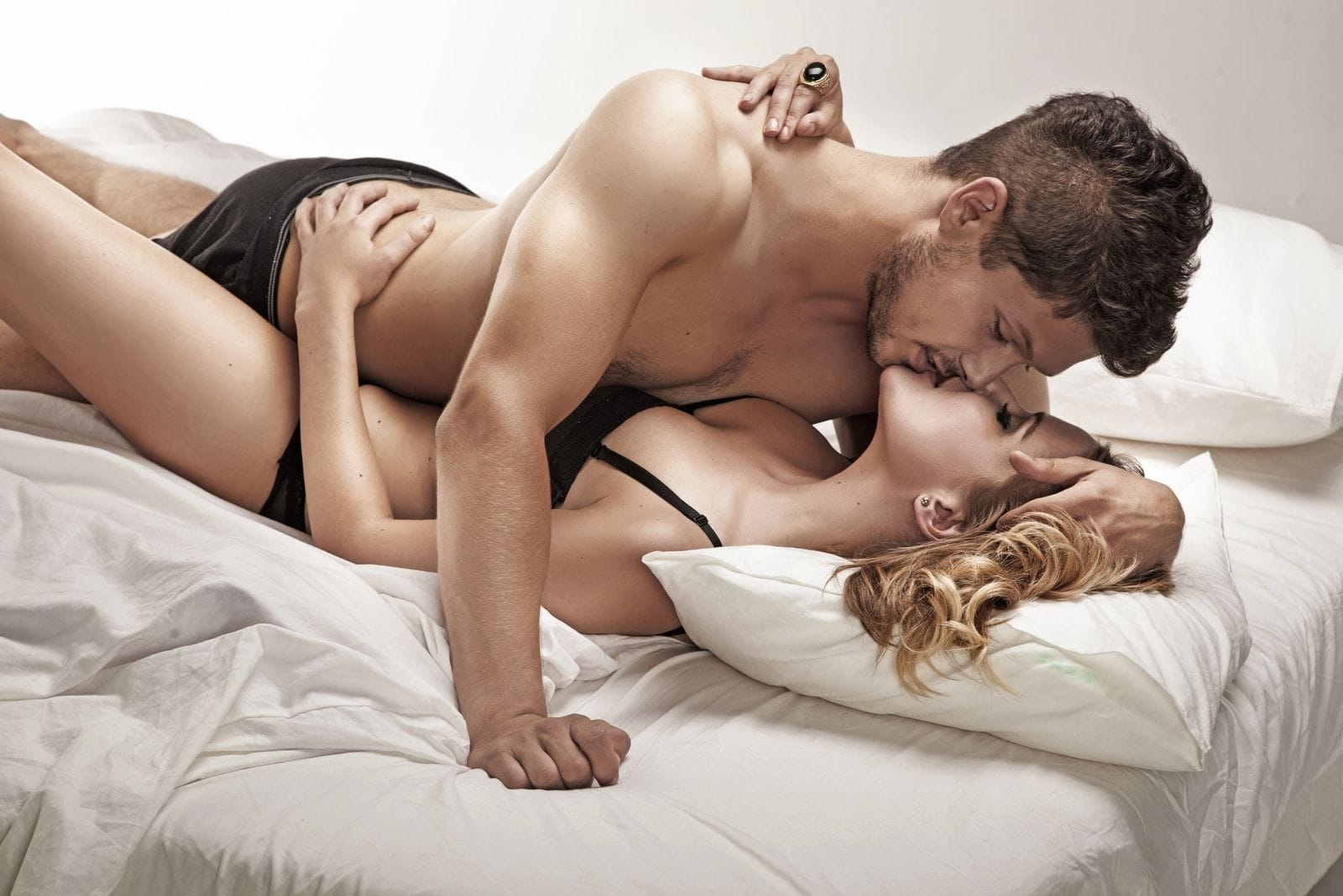 sexy young couple making love on top of the bed inside the bedroom