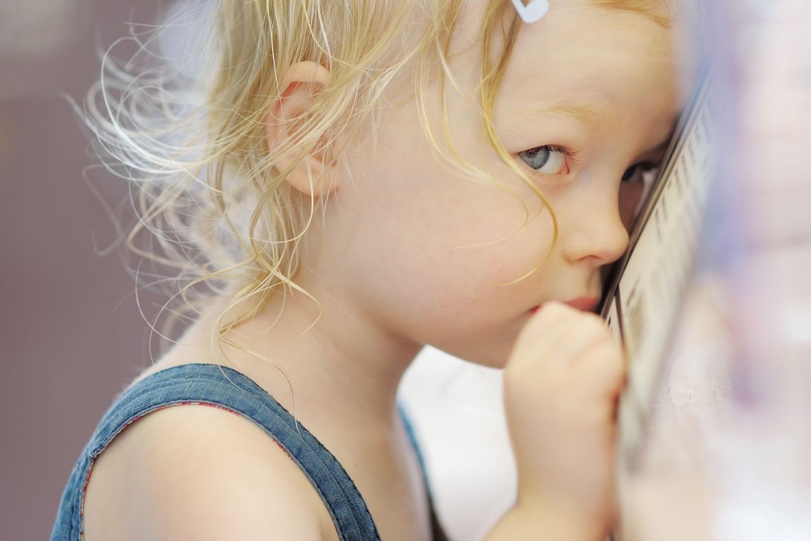 shy little girl portrait in the cafe hiding