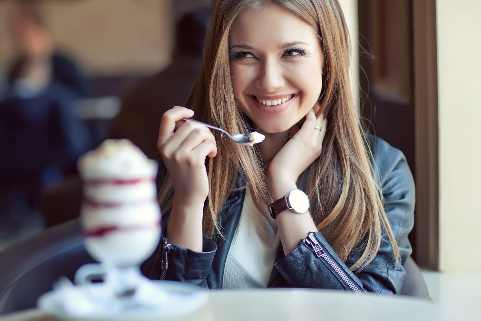 shy woman eating ice cream keeping her hair and smiling inside a cafe