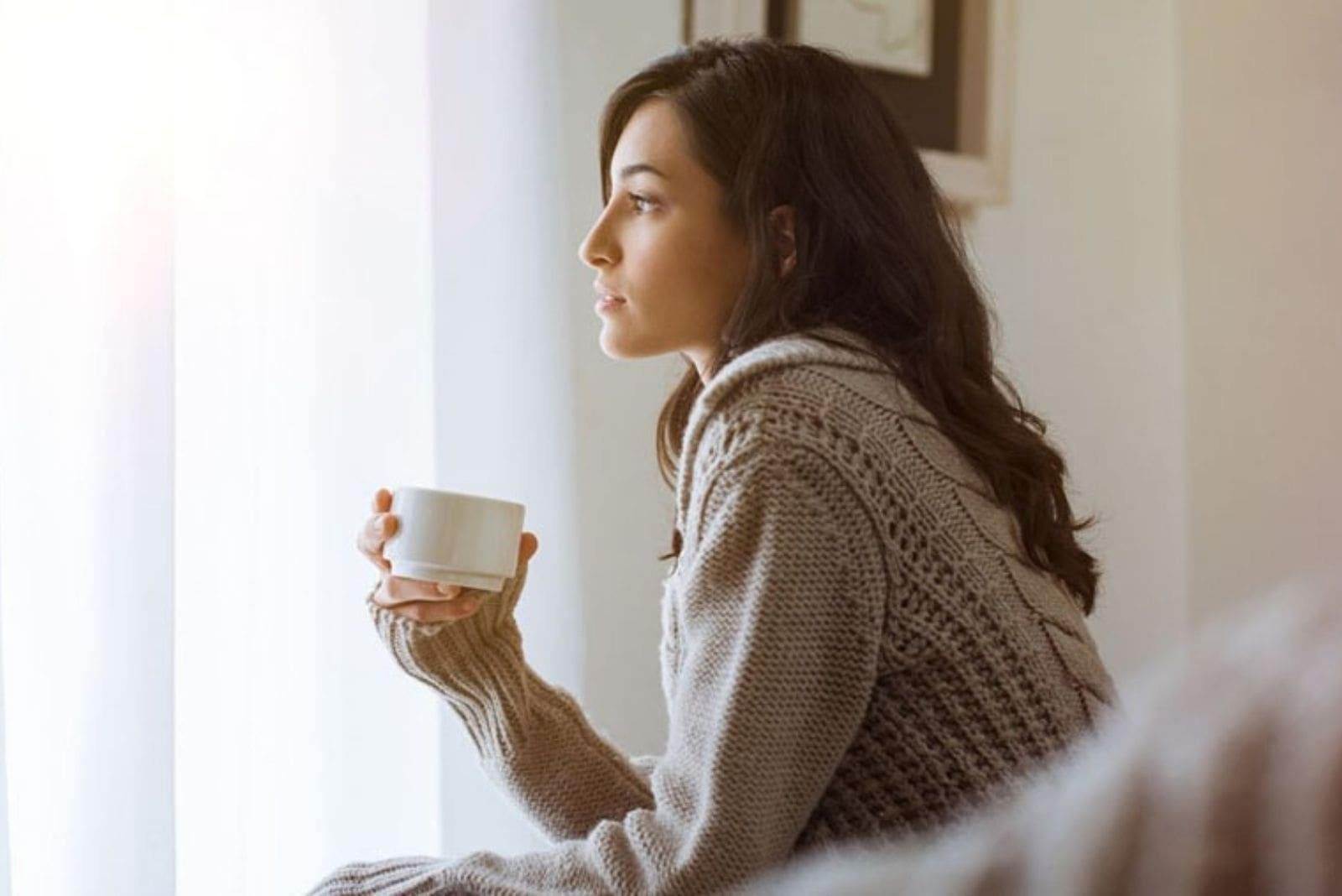 sideview of a young woman drinking coffee inside home looking out near the window pensively