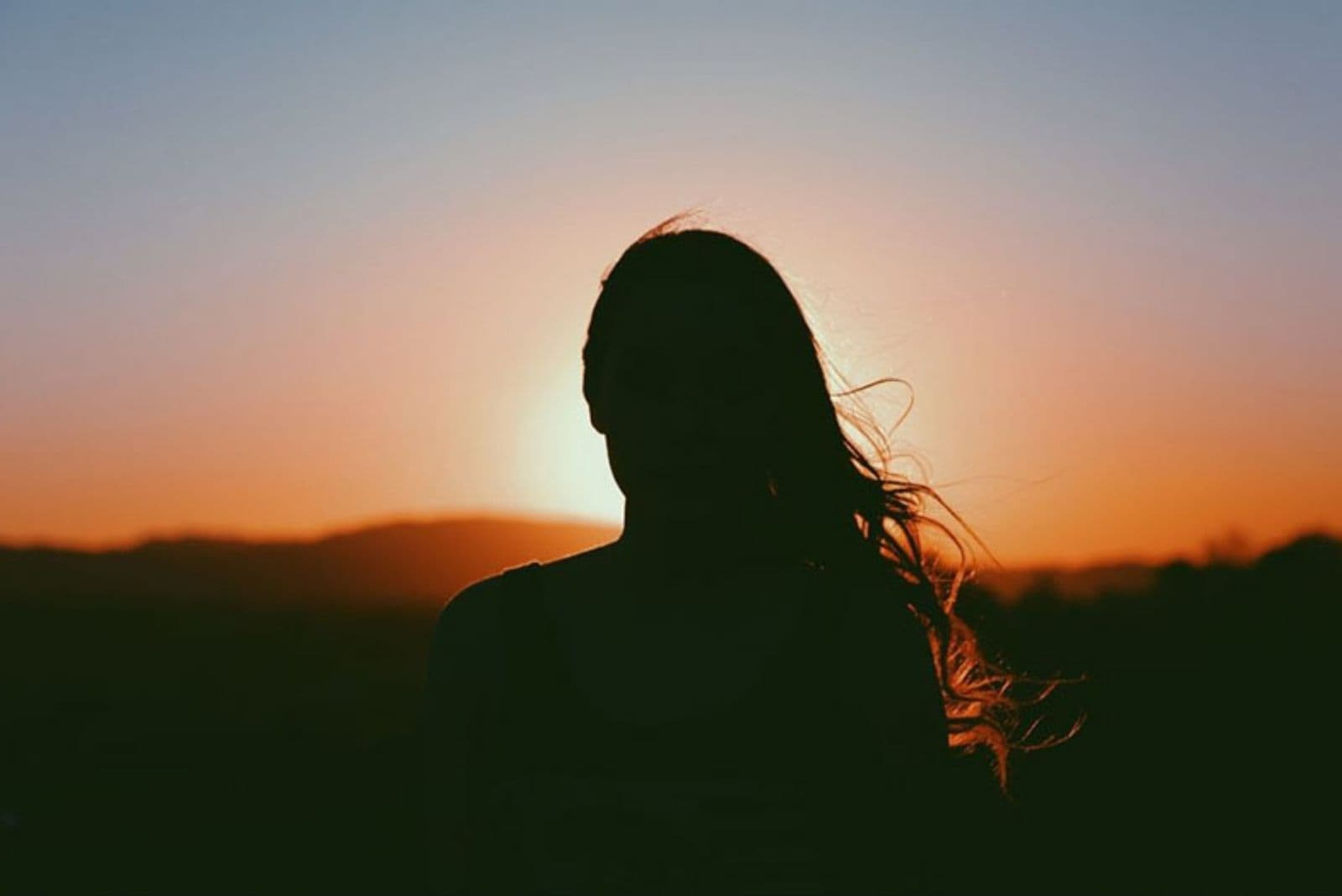 silhouette of a woman facing the sunset with hair partly blown by the wind