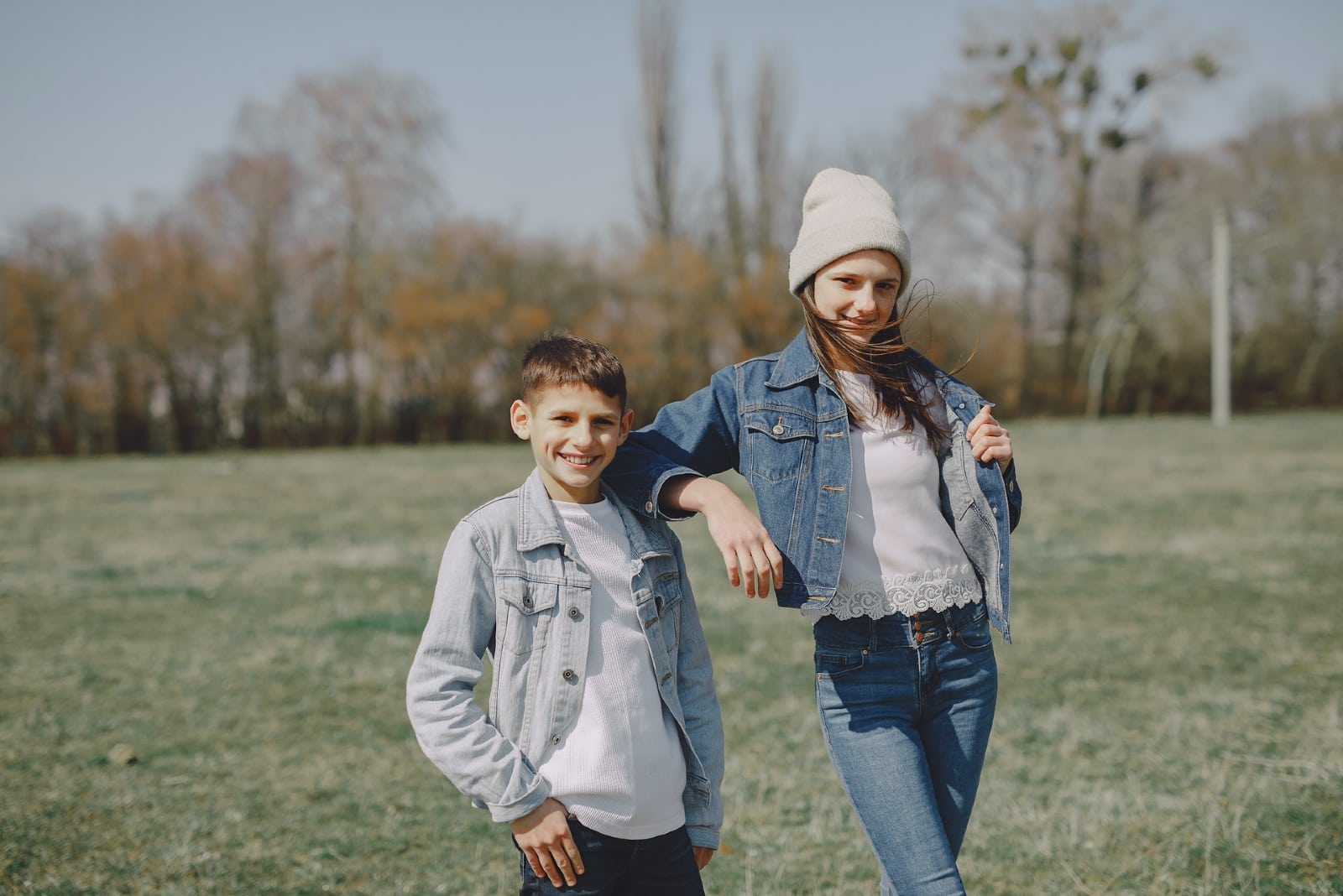 brother and sister in denim jackets standing on grass