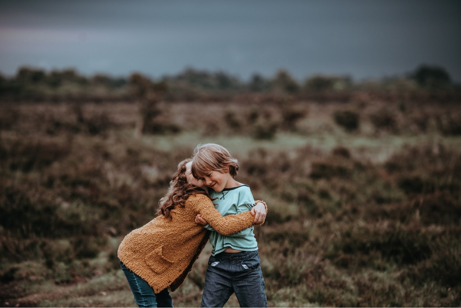 sister kissing brother while standing in the field