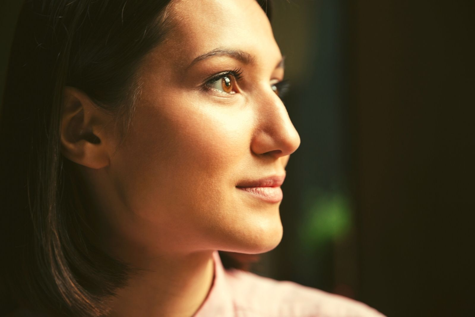 smiling brunette woman in sideview with focus of the face