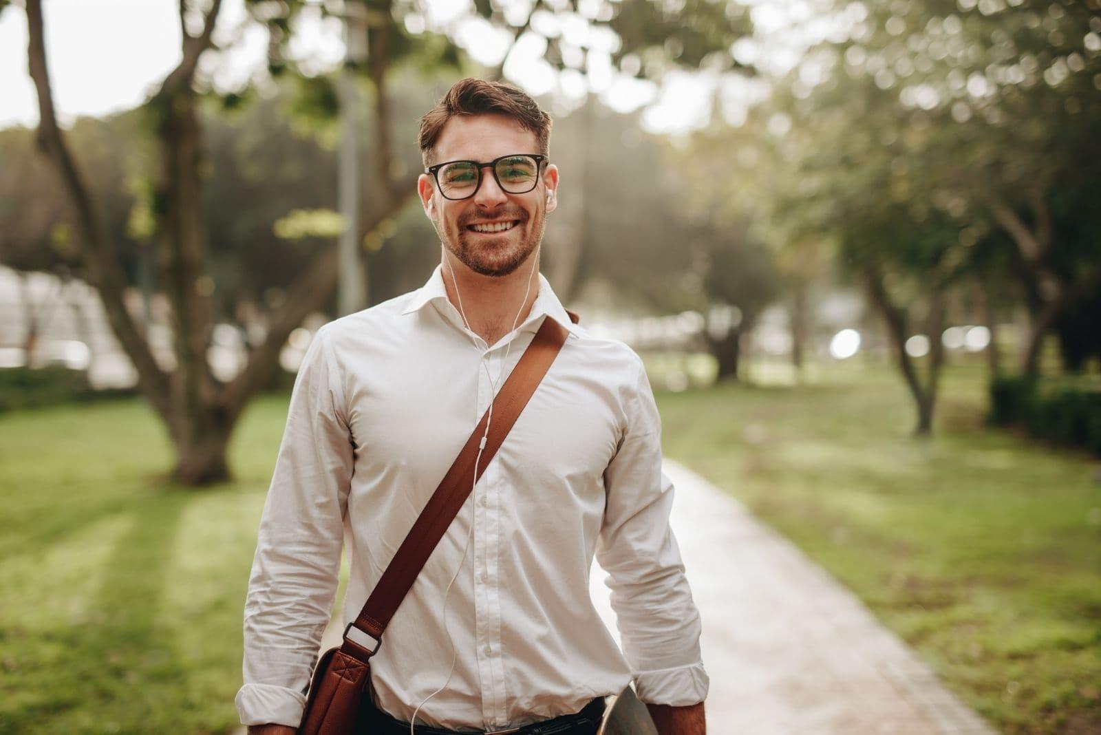smiling businessman walking outdoors carrying bag wearing eyeglasses