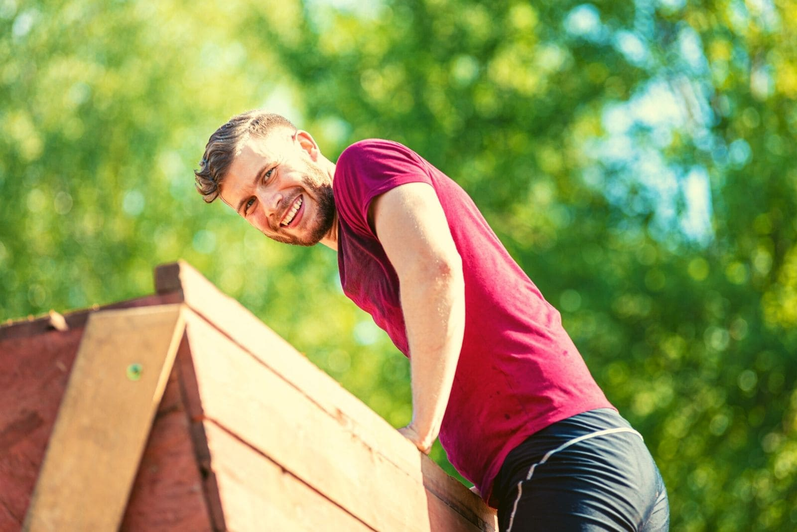 smiling man climbing over the obstacle at and extreme race at boot camp