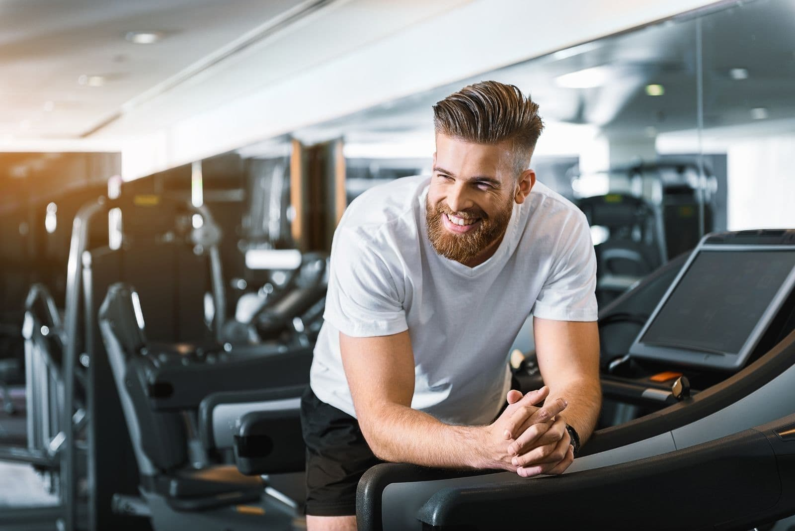 smiling man leaning on the side of the threadmill inside the gym